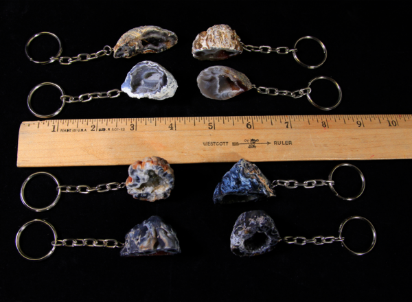 Eight Assorted Geode Keychains next to ruler for size comparison