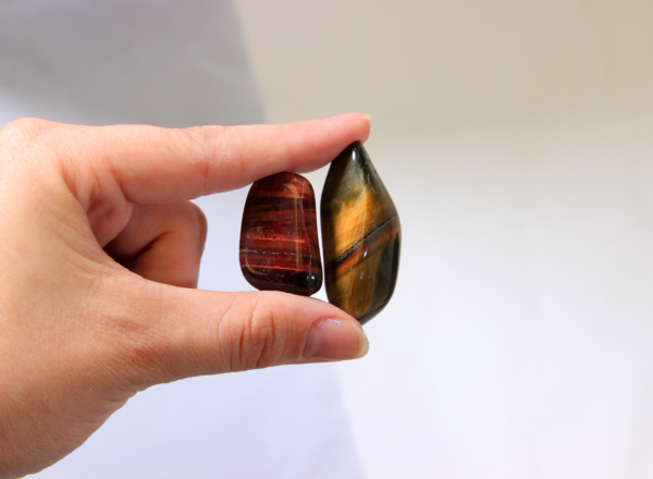 Two Red Tiger Eye Stones Held in hand for size comparison