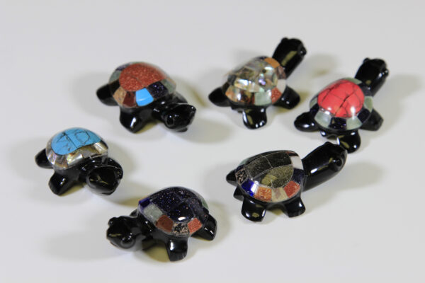 Six obsidian turtle figurines with assorted colored shells