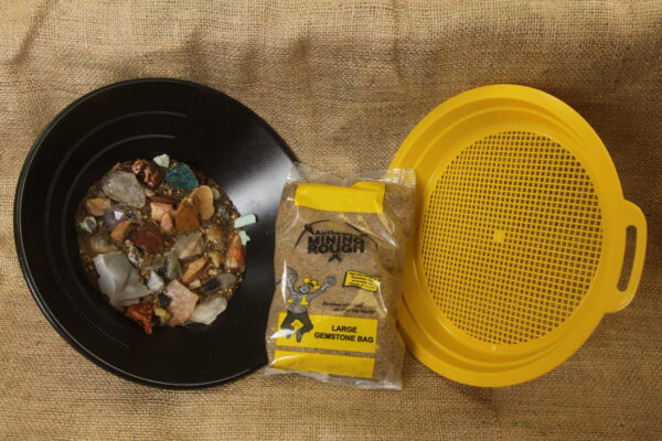 Assorted gems and crystals in sand with sifter