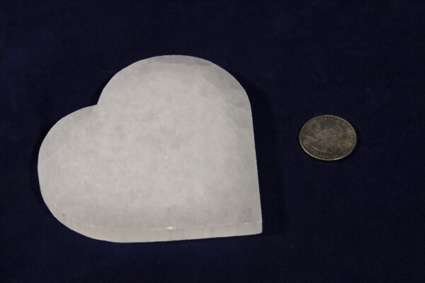 Heart-shaped selenite stone next to quarter for size comparison